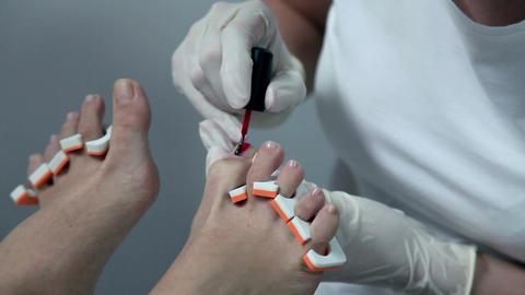 Applying red nail polish on toes ビデオ