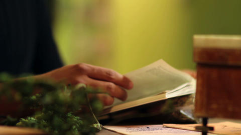 Close up of a man reading a book about herbs and h Live Action