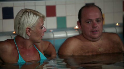 A couple in a swimming pool soaking and talking Footage