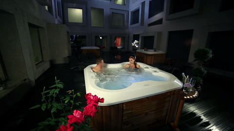 Young Couple Relaxed In Jacuzzi With Roses And Cha stock footage