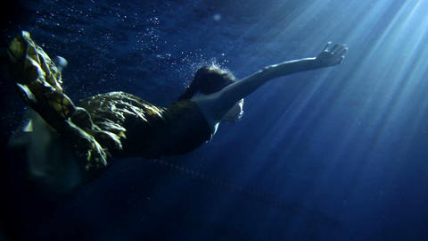 Young woman swimming under water in beautiful dres Footage