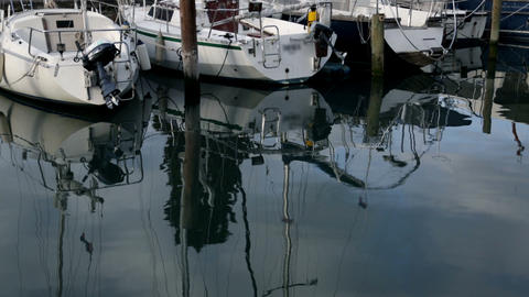 Reflection of sailboats in harbor on cloudy day Footage