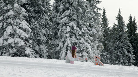 Teenaged girl and young child playing with snow Footage