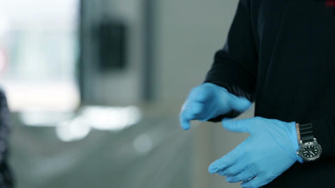Man putting on blue gloves Live Action