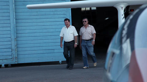 Close Up Of Two Man Coming From Airplane Hangar stock footage