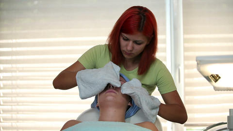 Removing the facial cream for further massage Footage