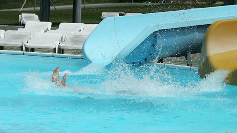 Colorful water slides in pool with people sliding  Live Action