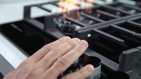 Hand turning on the gas cooker in kitchen Footage