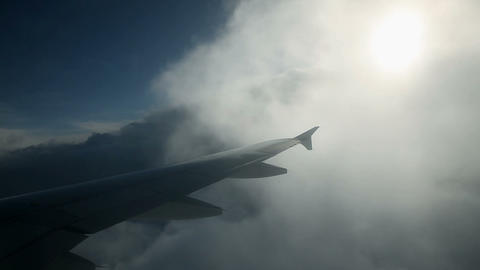 Passenger watching airplane flying through clouds Footage