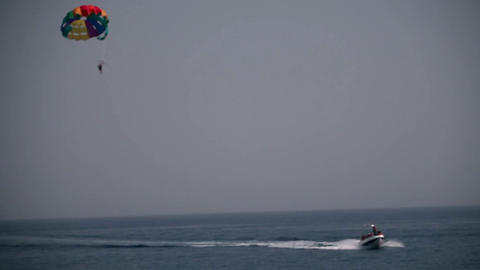 parachutist pulled by a boat over sea Footage