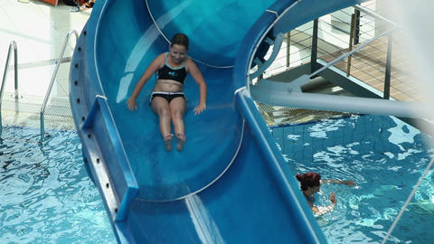 Young girl sliding down the waterslide Footage
