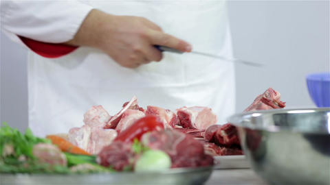 Cook cutting and adding red meat on green plate Footage