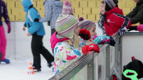Kids holding the fence of ice rink and talking to  Footage
