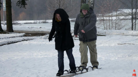 Two parents are walking on large skis without any  Footage