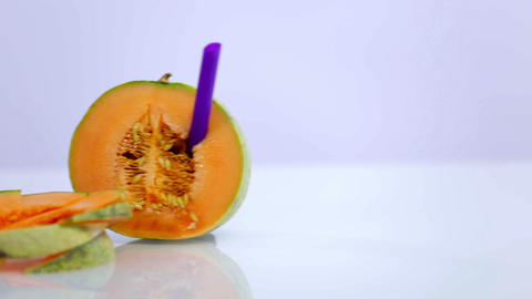 Melon and melon slices with violet straw on white  Footage