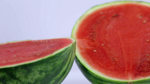Juicy watermelon is pierced with violet straw Footage