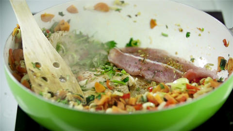 Meat falling onto vegetables in fyring pan Live Action