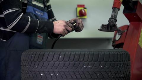 Vulcaniser fills a car's tire Footage