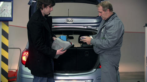Auto mechanic giving some tips to a young customer Footage