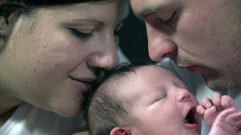Both parents kiss baby boy's head at the same time Footage