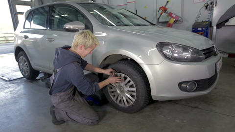 Auto mechanic is putting the tire back on a car Footage