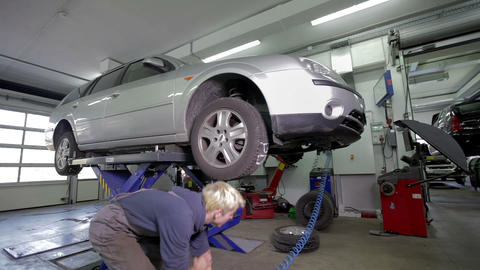 Blond mechanic removing tires for straightening Footage