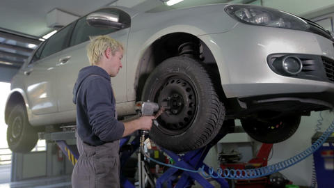 Vulcaniser loosening the screws on a tire Footage