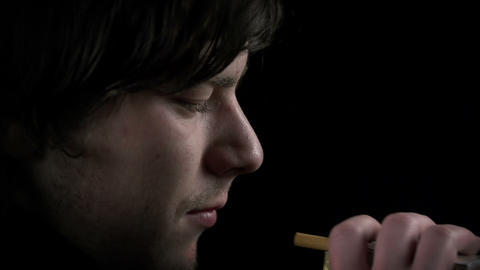 Detail shot of young man's face taking a cigarette Footage