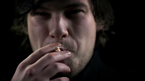 Young man inhales a cigarette smoke in slow motion Footage