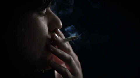 Side shot of young man's face inhaling cigarette s Footage