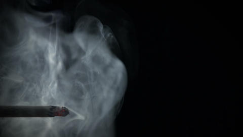 Cigarette with exhaled smoke brooding in the air Footage