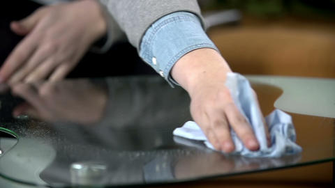 Cleaning the glass table with cloth and cleaning s Live Action
