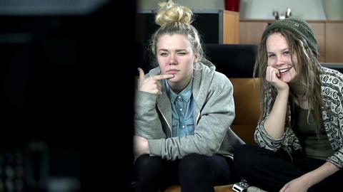 Pan shot of two teenagers watching TV programme Footage