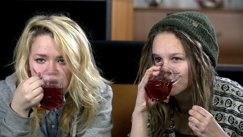 Girls make sips of tea in slow motion Footage