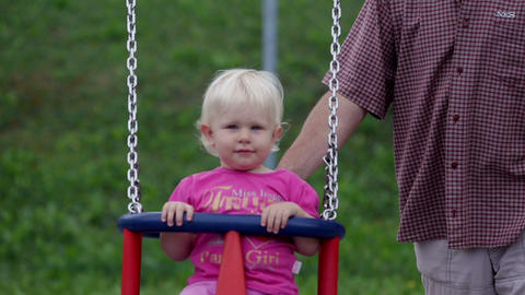 Grandfather swings little girl Footage