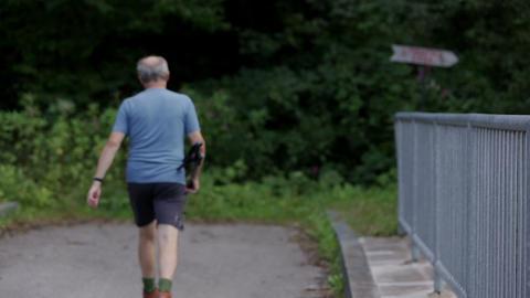 Trekker walks across the road bridge Footage