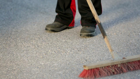 Worker sweeps the floor with a wide broom Live Action