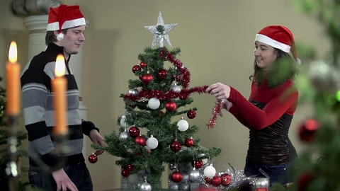 Domestic Christmas tree decorating with red ribbon Footage