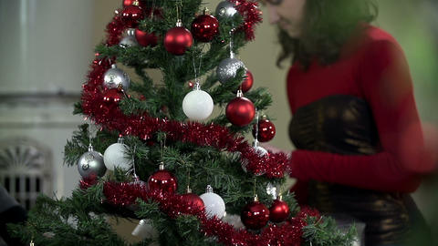 Girl hanging ribbons on Christmas tree in slow mot Footage