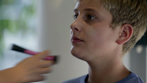 Putting powder on a kids face Footage