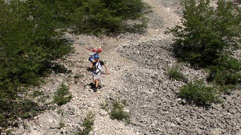 Two males walk down the scree slopes Footage