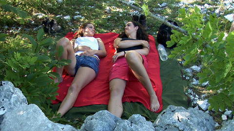 Two girlfriends lay on their backs in the nature a Footage
