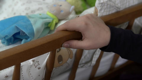 Detail of female hand rocking the infant bed Footage