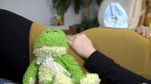 Puppet sits beside laying expectant mother laying  Footage