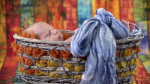 Baby sleeping in a basket with a blue bow Footage