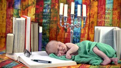 Baby covered in green blanket sleeps amid the book Footage
