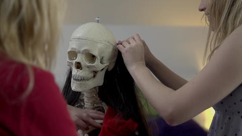 Girls Put The Hair On Skeleton's Skull stock footage