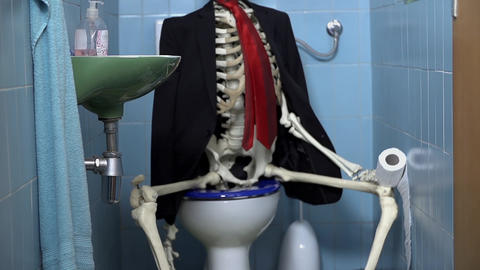 Skeleton sitting on the toilet having a number two Footage