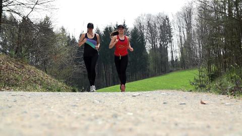 Two Female Runners Passing The Camera In Nature Tr Footage