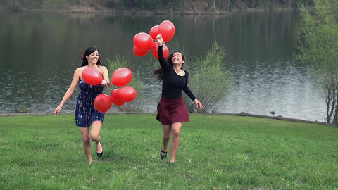 Two Girls Enjoying Life Running With Red Balloons  Footage
